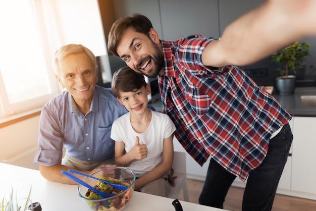 Um homem se fotografou, seu pai idoso e filho