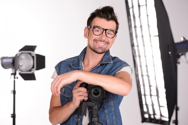 Um homem se levanta e sorri no estúdio para uma sessão de fotos.