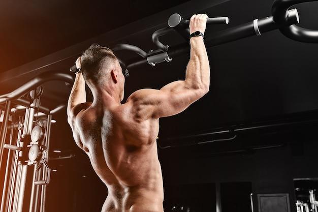 Um homem se levanta na academia no simulador, faz exercícios para diferentes grupos musculares