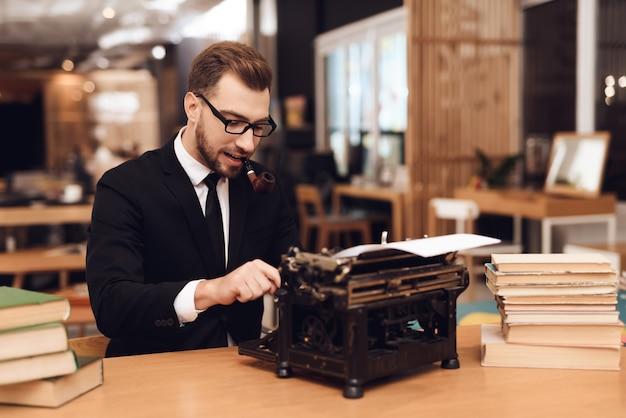Um homem se senta à mesa com uma velha máquina de escrever.