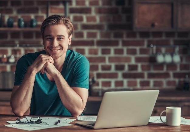 Um homem se senta à mesa e trabalha no laptop.
