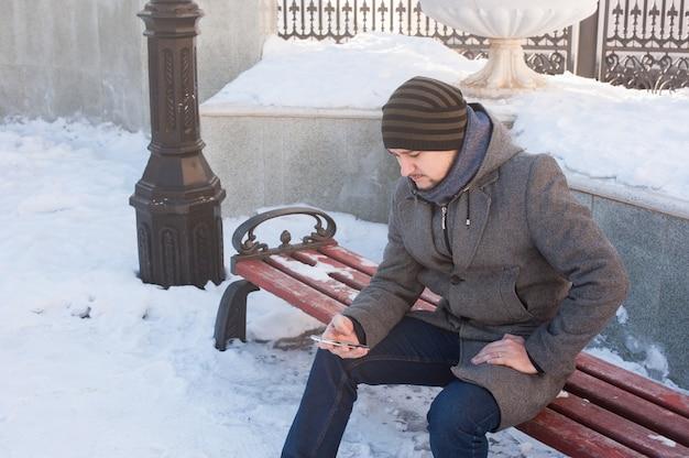 Um homem se senta em um banco e olhando para o telefone