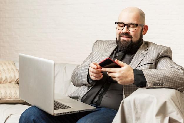 Um homem se senta em um sofá com um laptop no colo. blogging e treinamento.