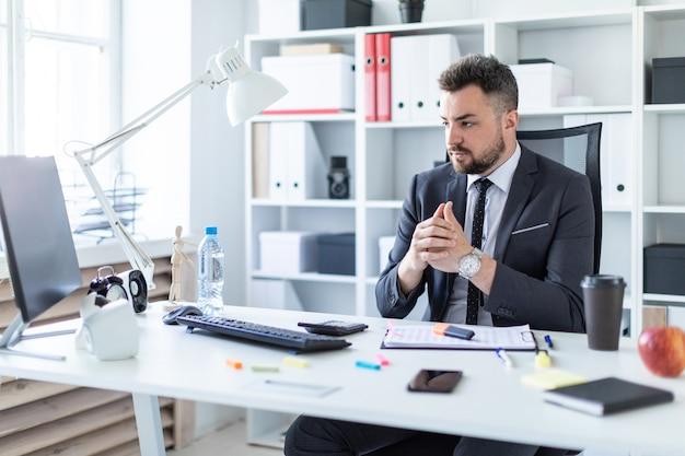 Um homem se senta em uma cadeira no escritório à mesa e olha para o monitor.