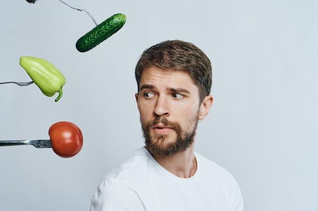 Um homem se senta em uma mesa com legumes e frutas, alimentação saudável, veganismo, veggie