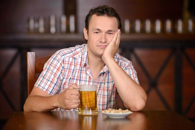 Um homem se senta em uma mesa e bebe cerveja em um bar.