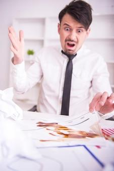 Um homem se senta em uma mesa e é surpreendido do trabalho.