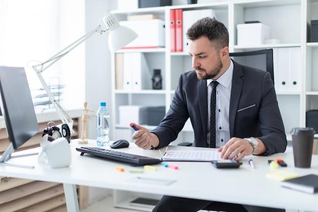 Um homem se senta no escritório à mesa e clica em uma caneta.