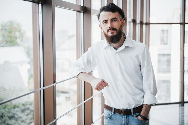 Um homem sedutor em uma camisa branca, olhando para a câmera.