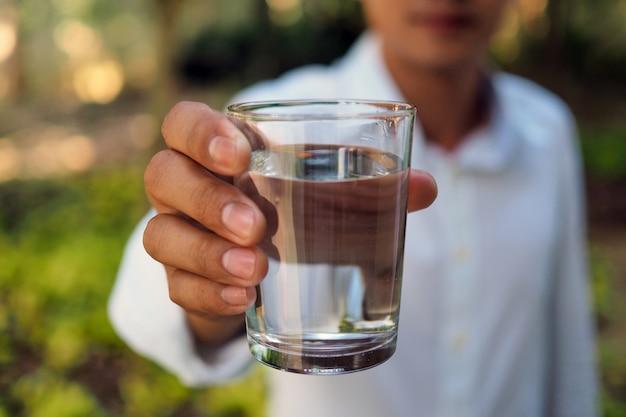 Um homem segura a água para beber.
