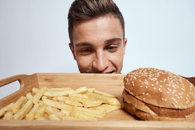 Um homem segura à sua frente uma palete de batatas fritas, hambúrguer, estilo de vida fast food comendo