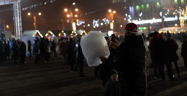 Um homem segura algodão doce, uma criança olha para ele