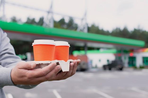 Um homem segura duas xícaras de café em um posto de gasolina.