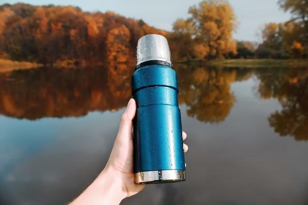 Um homem segura na mão uma garrafa térmica azul, da floresta de outono e do lago.