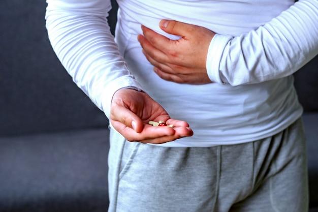 Um homem segura o estômago, estica a mão com comprimidos. saúde, doença, remédio.