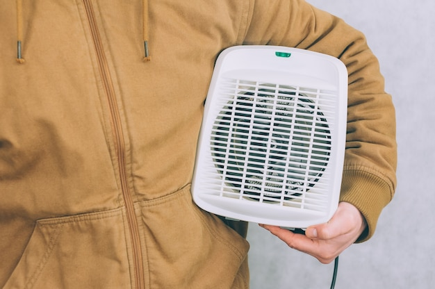 Um homem segura um aquecedor nas mãos sobre uma luz.