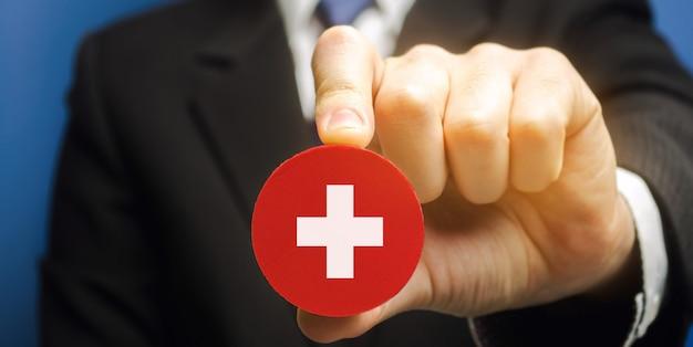 Um homem segura um bloco com uma cruz médica. conceito de saúde, medicina e caridade. plano de saúde