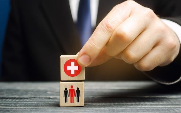 Um homem segura um bloco com uma cruz médica e pessoas. conceito de saúde, medicina e caridade.
