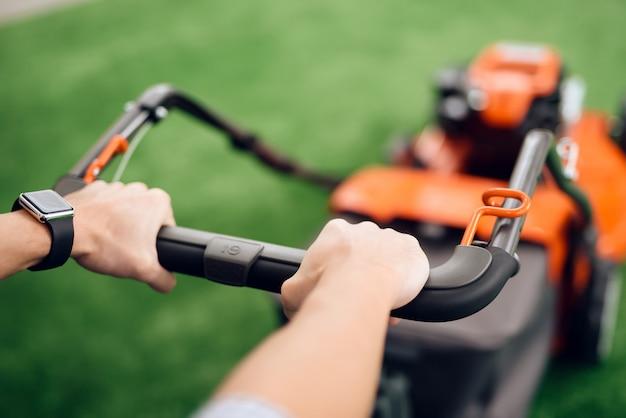 Um homem segura um cortador de grama para o punho.