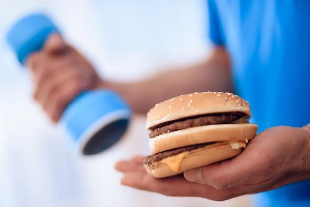 Um homem segura um hambúrguer em uma mão, em outro haltere.