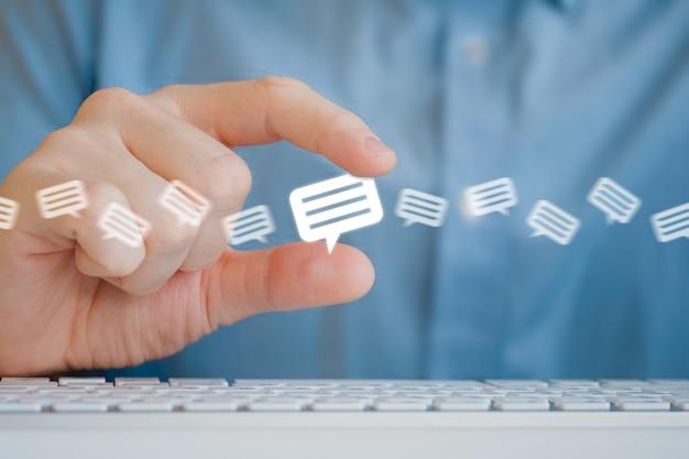 Um homem segura um ícone de mensagem com os dedos. o processamento de recursos e revisões.