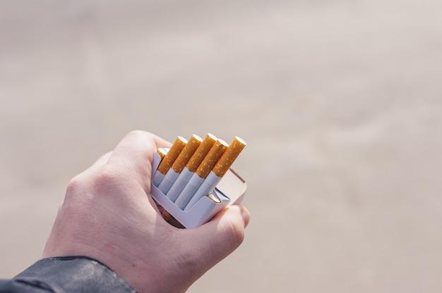 Um homem segura um maço de cigarros nas mãos.