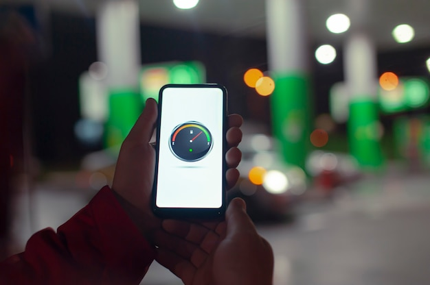 Um homem segura um smartphone com um medidor digital de combustível na tela no contexto de um posto de gasolina noturno para um carro.