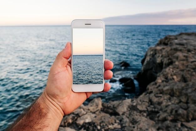 Um homem segura um telefone celular, tirando uma foto de uma paisagem de mar e rochas