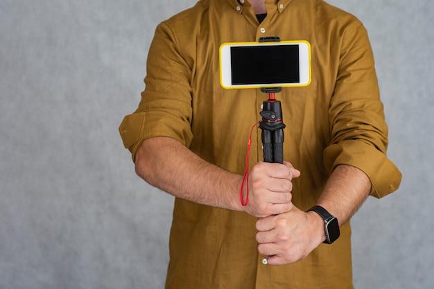 Um homem segura um tripé flexível com a maquete de um smartphone com tela preta.