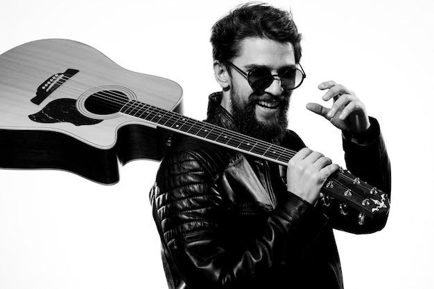 Um homem segura um violão nas mãos, posando com uma jaqueta de couro preta e óculos escuros
