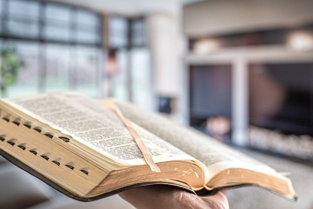 Um homem segura uma bíblia contra a parede da sala de estar.