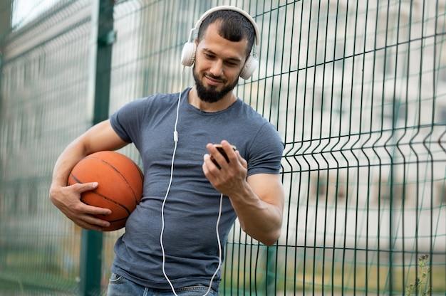 Um homem segura uma bola de basquete na mão, olha para um smartphone e ouve música com fones de ouvido na rua