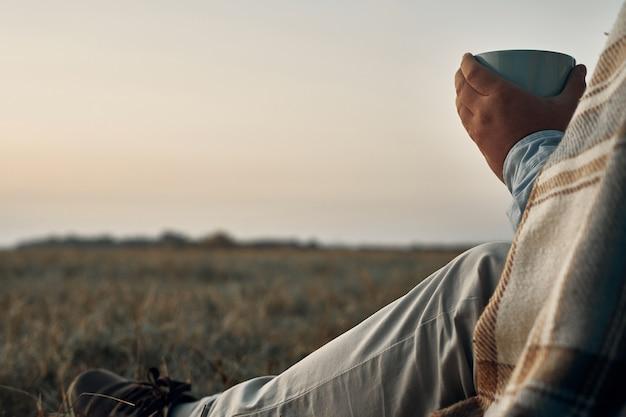 Um homem segura uma caneca nas mãos e olha para o amanhecer. viajante, nascer do sol.