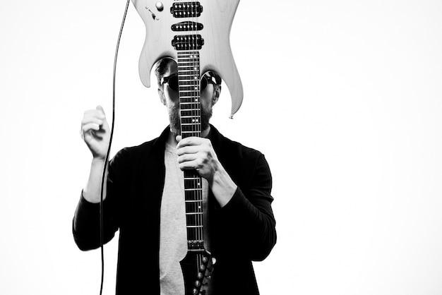 Um homem segura uma guitarra nas mãos música emoções jaqueta de couro preta óculos escuros luz do estúdio