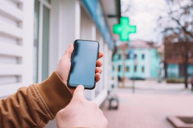 Um homem segura uma maquete de um smartphone no fundo de uma farmácia na cidade.
