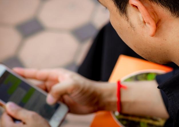 Um homem segurando e mandando uma mensagem no display touchscreen do smartphone. homem asiático usando o aplicativo para conversar. mídia social viciada.
