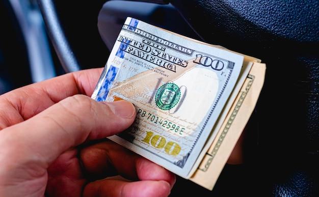Um homem segurando notas de dólares americanos na mão com a nota de cem dólares em destaque