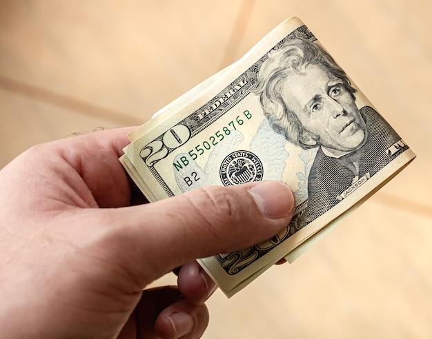 Um homem segurando notas de dólares americanos nas mãos com a nota de vinte dólares em destaque
