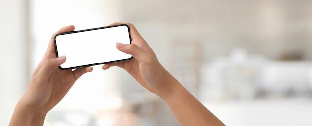 Um homem segurando o smartphone de tela em branco horizontal no escritório turva