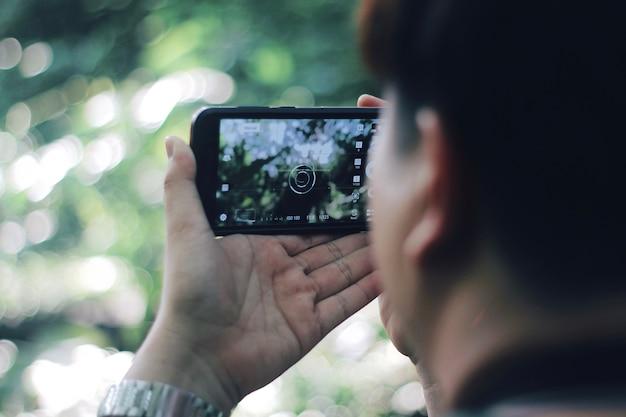 Um homem segurando o telefone inteligente tirando foto abstracr