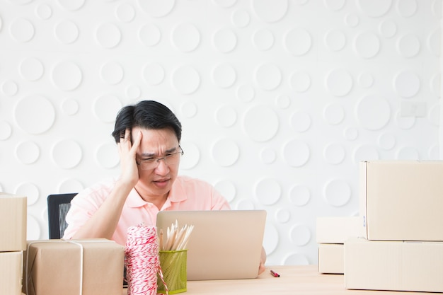 Um homem segurando sua cabeça como se estivesse com dor de cabeça enquanto olha para um notebook.