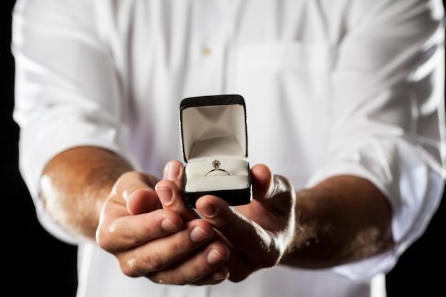Um homem segurando um anel de diamante em um gesto de doação.