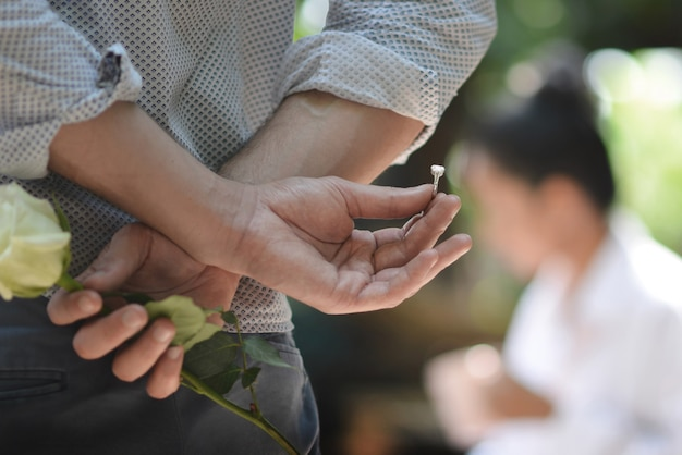 Um homem segurando um anel e levantou-se atrás dele para dar e propor a uma mulher