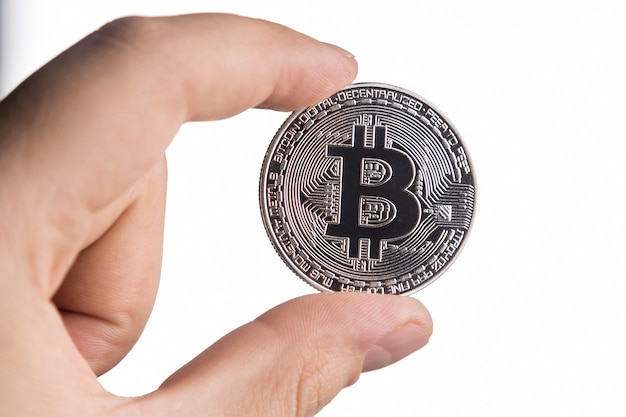 Um homem segurando um bitcoin de prata