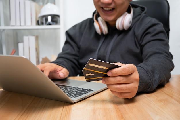 Um homem segurando um cartão de crédito fictício e usando um laptop para pagamento online