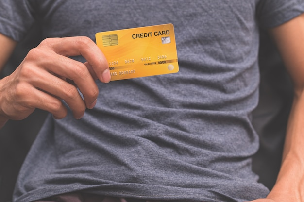 Um homem segurando um cartão de crédito na mão