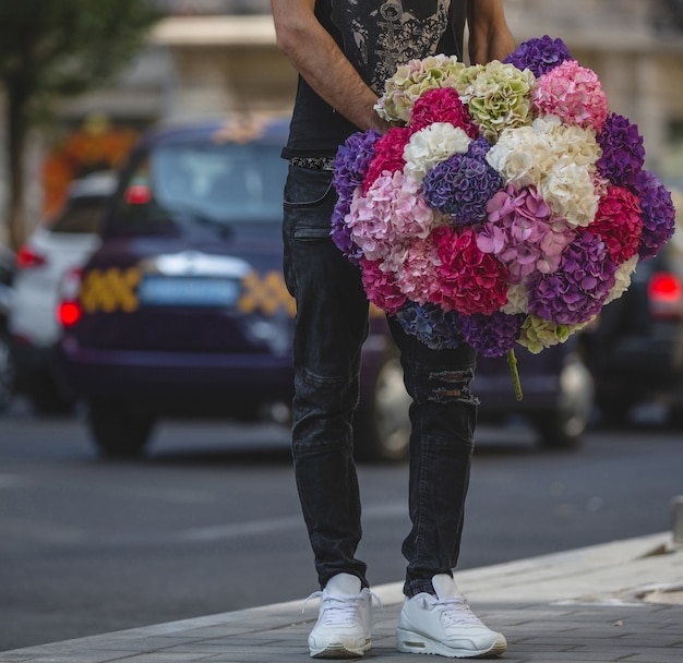 Um homem segurando um grande buquê de crisântemos coloridos na rua.