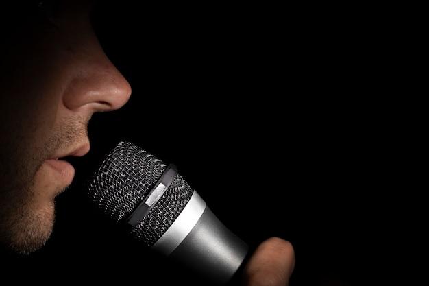 Um homem segurando um microfone em uma superfície preta