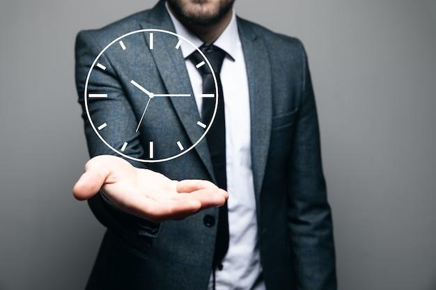 Um homem segurando um relógio virtual em uma cena cinza
