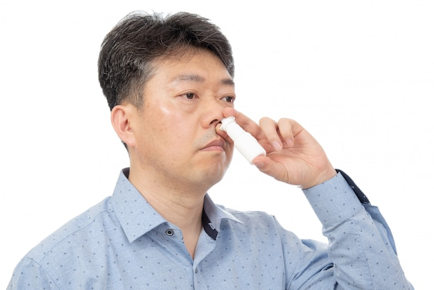 Um homem segurando um spray nasal na mão